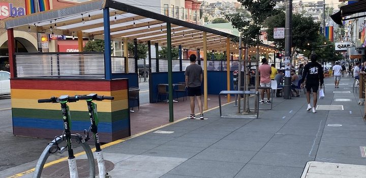 """Outdoor dining on Castro Street in a rainbow """"parklet"""""""